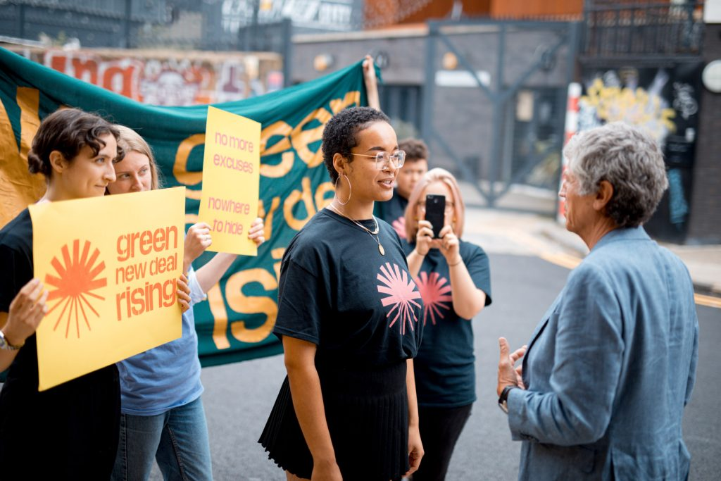 Image depicts a young woman wearing a t-shirt with the green new deal rising logo, flanked by friends holding banners and placards which say 'no more excuses'. She is confronting her MP, a man in a grey blazer.