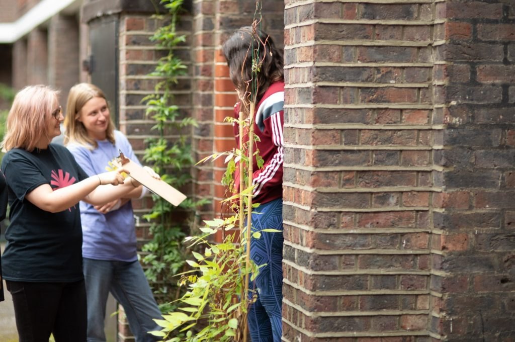 Image shows two green new deal rising organisers speaking to a woman in a red hoodie on her doorstep - they are asking her to sign a petition on their clipboard.
